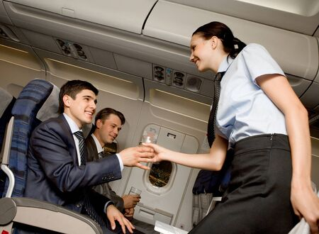 Kind stewardess giving glass of water to young businessman in airplane Stock Photo - 8507960