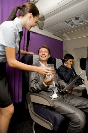 Image of pretty stewardess giving glass of water to successful businessman in airplane photo