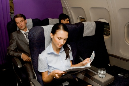 adult magazines: Image of pretty girl reading magazine in airplane with sleeping men behind Stock Photo