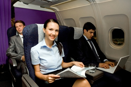 business trip: Image of pretty girl with magazine looking at camera while handsome man typing next to her