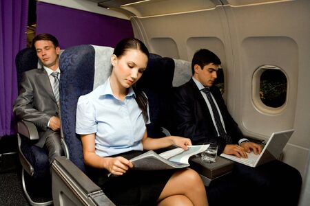 airplanes: Image of pretty girl reading magazine while handsome man typing next to her