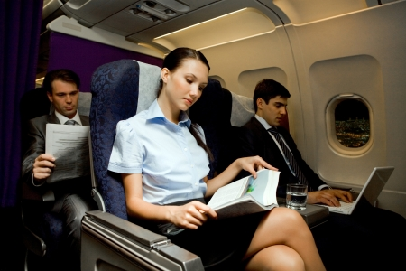 passenger plane: Image of pretty girl reading magazine while handsome man typing next to her in airplane Stock Photo