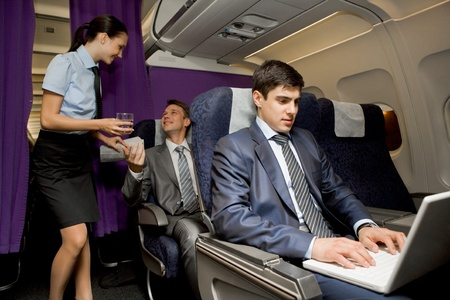 passager: Image of busy male typing on laptop with pretty stewardess giving glass of water to successful businessman on background