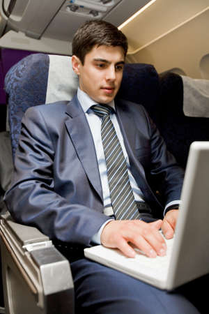 Image of busy male typing on laptop during flight photo