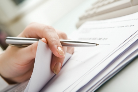 hand holding pen: Close-up of  hand holding pen with paper over pile of documents