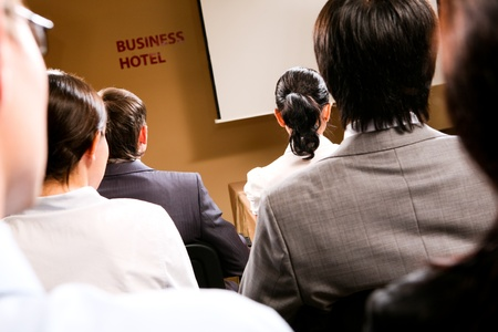 Rear view of business people listening attentively while sitting at conference photo