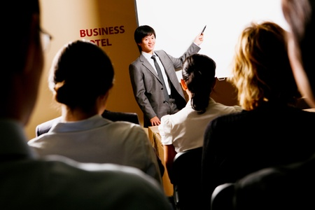 briefing: Image of confident businessman explaining something on whiteboard during conference