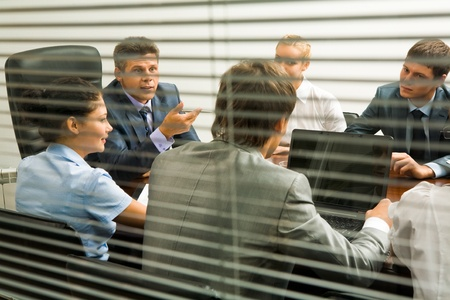 Above view of young co-workers interacting with each other at meeting photo