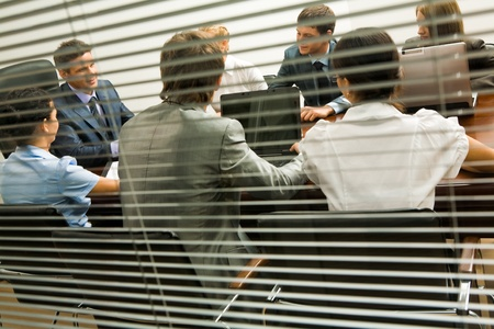View from behind venetian blind of associates interacting at working meeting photo