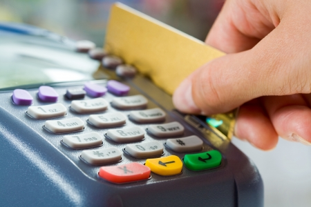 debit card: Close-up of payment machine buttons with human hand holding plastic card near by