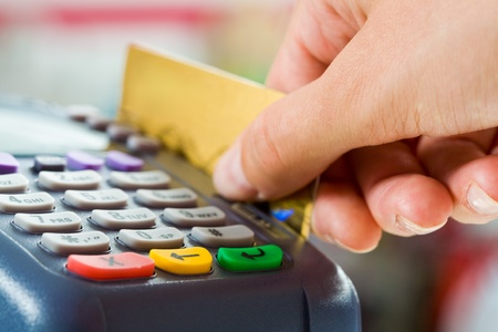 debit: Close-up of payment machine buttons with human hand holding plastic card near by