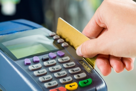 debit card: Close-up of payment machine while human hand keeping plastic card in it