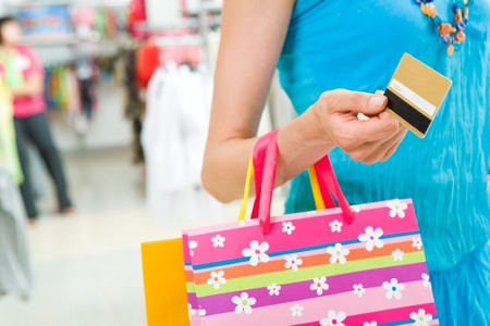 shoppingbag: Close-up of woman's hand holding plastic card while going shopping in the mall Stock Photo