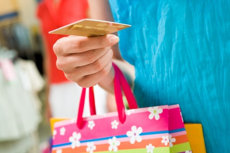pay for: Image of female holding card in hand ready to pay for her shopping