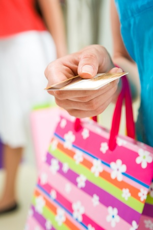 Image of woman�s hand giving plastic card in the mall photo