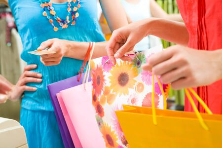 Close-up of woman�s hand holding credit card and bags with another female near by during shopping in the mall Stock Photo - 8508050