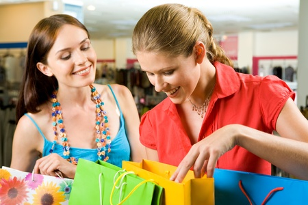 shoppings: Photo of two friends looking through their shoppings with smiles in the mall