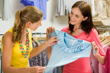 Image of pretty shop assistant showing blue tanktop to beautiful girl in the department store photo
