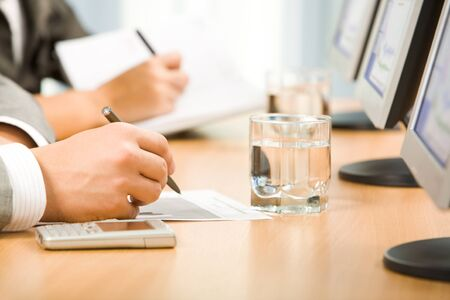 hand holding pen: Image of human hand holding pen and making notes with glass of water and monitors near by Stock Photo