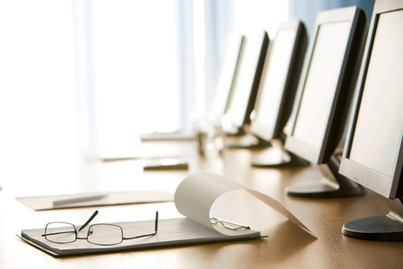 computer classroom: Image of workplace with paper, eyeglasses and monitors near by Stock Photo