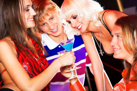 Portrait of amorous couple with drinks in hands looking at each other on background of smart friends photo
