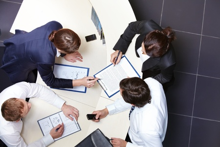 collaboration: Above view of several business partners discussing business plan