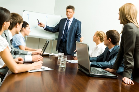 Image of smart business people listening to confident man while he explaining something on whiteboard during seminar photo