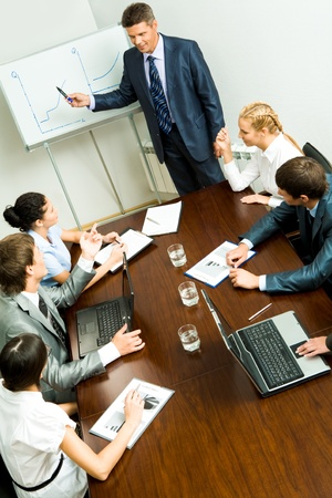 a communication: Above angle of business people listening to confident man during seminar Stock Photo