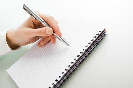 Image of hand with pen over notepad photo