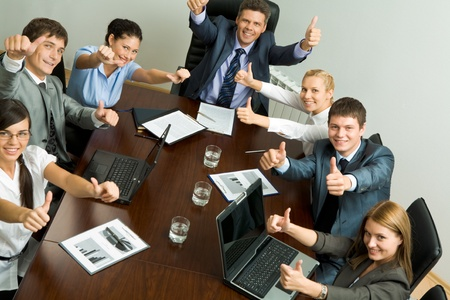 Portrait of business people showing thumbs up and looking at camera photo