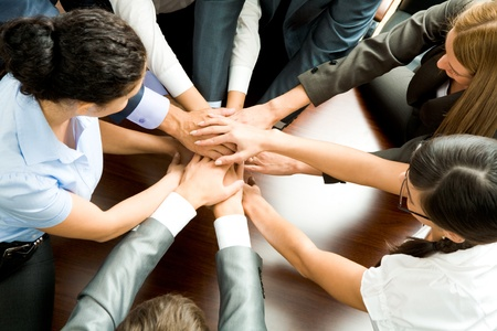 partnership power: Above angle of business partners making pile of hands on workplace   Stock Photo