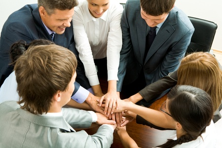 Photo of happy business partners making pile of hands on workplace   photo