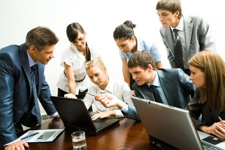 Image of company of successful partners looking at laptop monitor while successful man pointing at it Stock Photo - 8508159