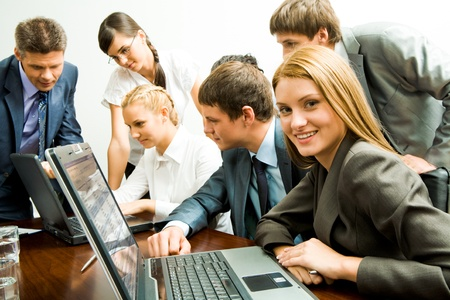 Image of smiling female on background of company of successful partners looking at laptop monitor photo
