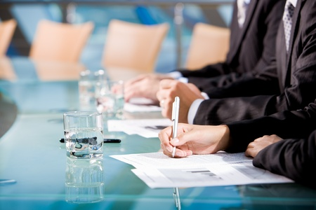 conferentie: Rij van menselijke handen houden pen en het maken van notities met glas water in de buurt van door