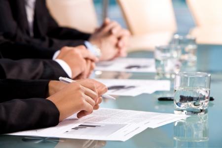 revisando documentos: Fila de manos humanas en los lugares de trabajo con documentos durante la Conferencia