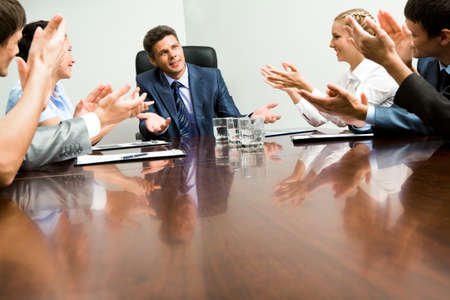 Photo of happy business partners applauding to confident leader at meeting photo
