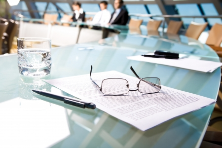 eyeglasses: Image of several objects lying on the table in the conference room