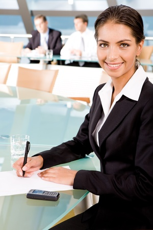 Portrait of beautiful woman writing on the background of two businesspeople in conference room photo