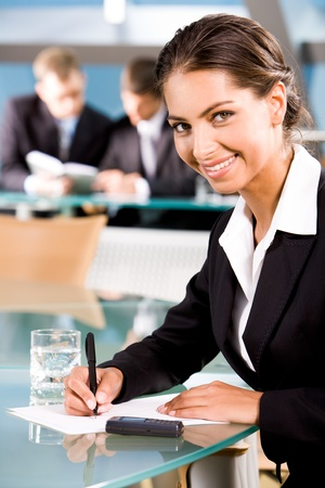 Portrait of beautiful woman looking at camera on the background of two businesspeople in conference room photo