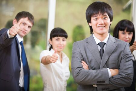 Portrait of smiling businessman looking at camera with successful group behind photo