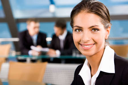 Close-up of beautiful woman smiling on the background of two businesspeople photo