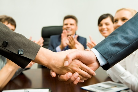 applauding: Photo of successful business partners handshaking after striking great deal with applauding people at background