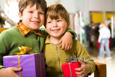 Portrait of cute boy with giftbox embracing his brother in supermarket photo