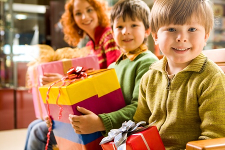 newyear: Happy boy with gift in hands sitting in supermarket on background of his brother and mother Stock Photo