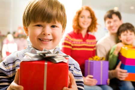 glad: Portrait of glad boy with present looking at camera on background of family members