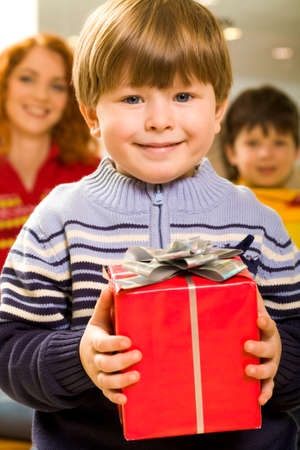 Portrait of glad boy with present looking at camera and smiling photo