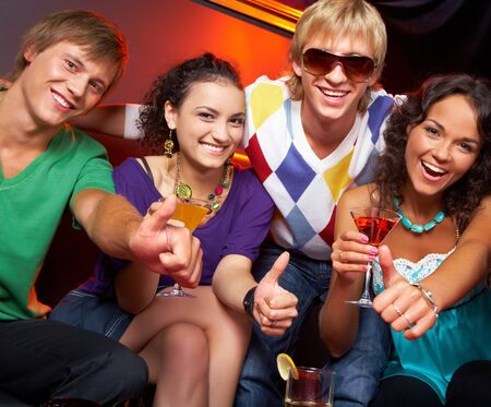 altogether: Portrait of young people with flutes showing thumbs up in the nightclub Stock Photo