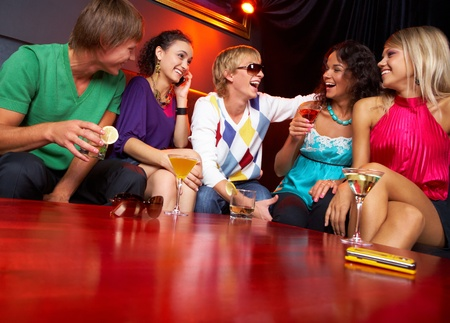Portrait of friends sitting on the sofa and chatting in the nightclub photo
