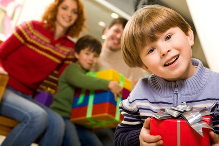 Portrait of laughing boy with nice present on background of his parents and brother photo